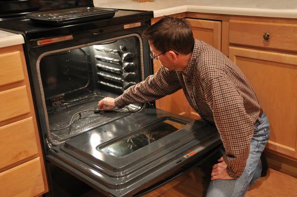 Частный мастер ремонтирует духовку